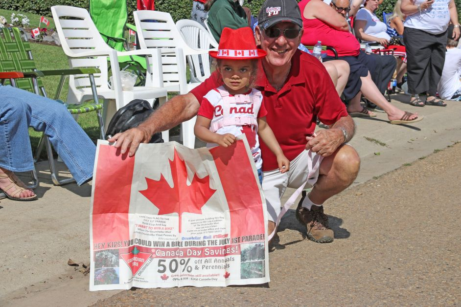 Canada Day parade goers show off their Drumheller Mail Canada Day flag in the hopes of winning a new bike. (mailphoto by Pat Kolafa)