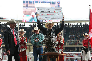 Big Valley native Zeke Thurston holds up his third consecutive cheque of $100,000 from the Calgary Stampede